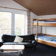 Zimmerbeispiel II. OG mit Etagenbetten und gemütlicher Couch